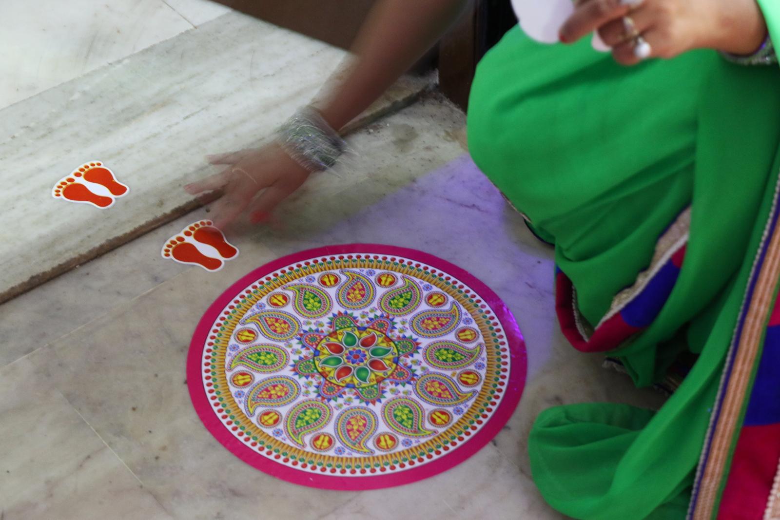 Ulko-oven eteen tehdään perinteisesti rangoli-kuvio värjätystä riisijauhosta. On olemassa myös tällainen kätevä tarra-rangoli, joka ei sotkeudu, kun lapset juoksevat sisään ja ulos! Settiin kuuluvat myös jalanjäljet kynnyksen molemmille puolille. Niitä pitkin Lakshmi, hindulainen vaurauden jumalatar, löytää sisään.